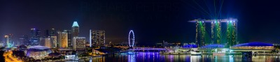 A panoramic showing the incredible lights show of the Marina Bay Sands hotel in Singapore, and partial skyline across the bay.